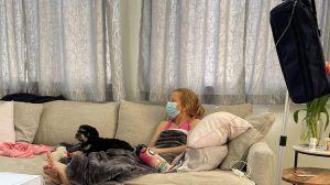 Bendel sits beside Alex while she receives a home drug infusion.